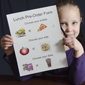 Child holding pre-order for school lunch.