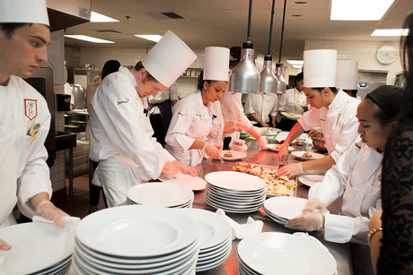 Students preparing food in the kitchens at the 88th (2013) Hotel Ezra Cornell Gala Banquet.