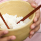 Child holding bowl of rice